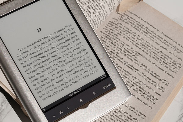 e-reader on top of book with a marked page