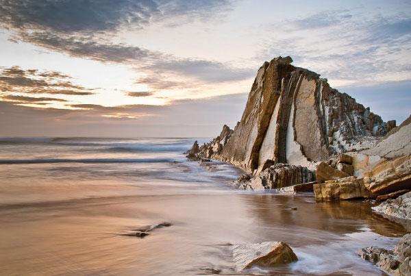 Ocean sunrise next to a tall rock