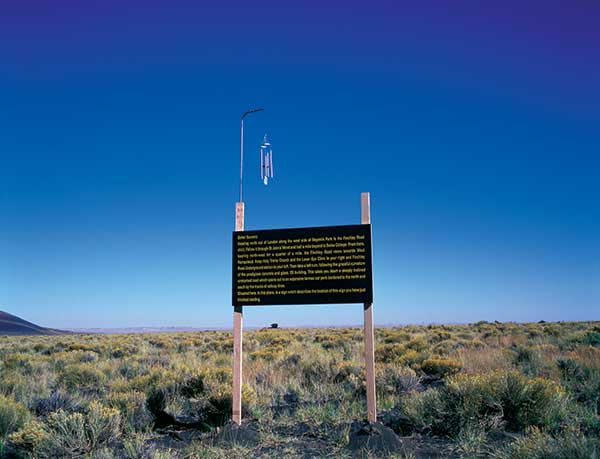 """Better Scenery, 2000,"" by Adam Chodzko, presents language in the landscape, but it refers to elsewhere. Here in the Painted Desert, the reader finds directions from central London to another sign in the O2 shopping center car park. The wind chime atop the sign alerts the reader's body to here."