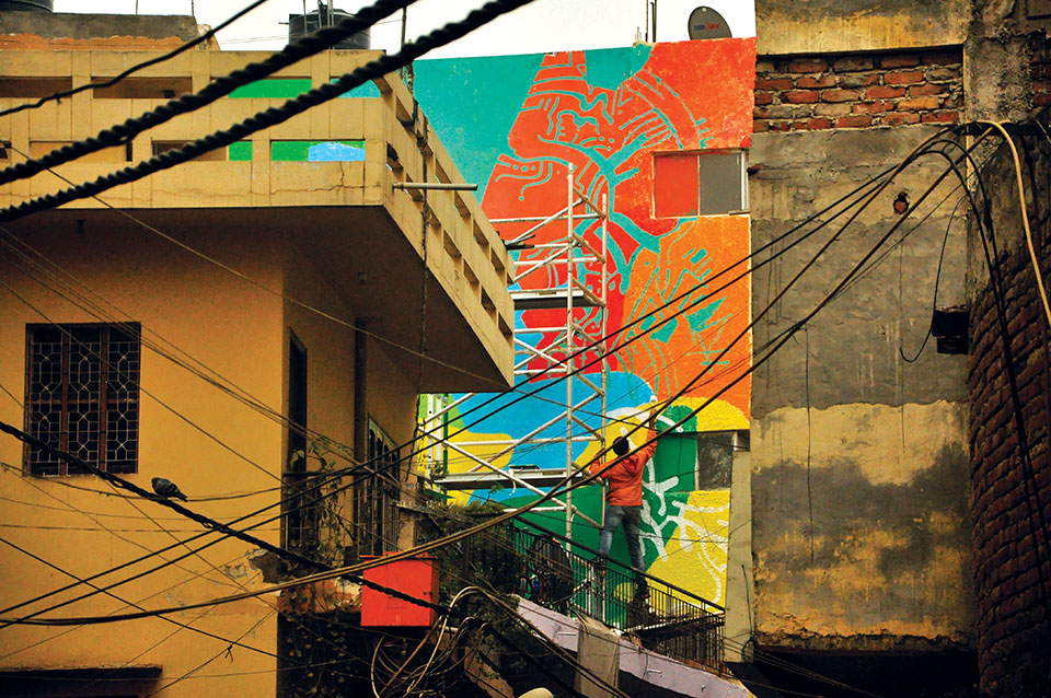 An artist adds color to a building in a Delhi alleyway. Photo by Vikram Kapur.