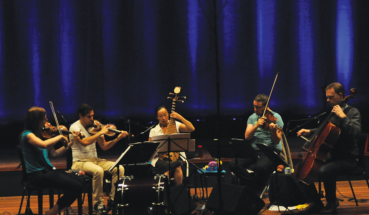 Liu Fang (center) plays the pipa during a rehearsal with fellow musicians.