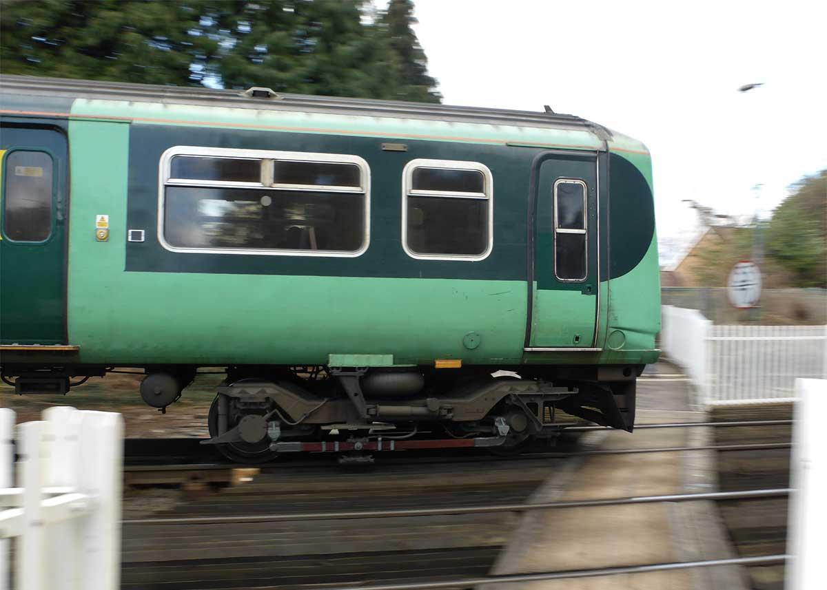 Green train passing platform outside