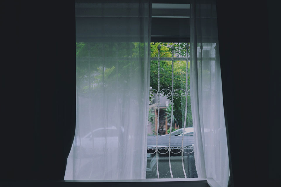 An open window with loose white curtains