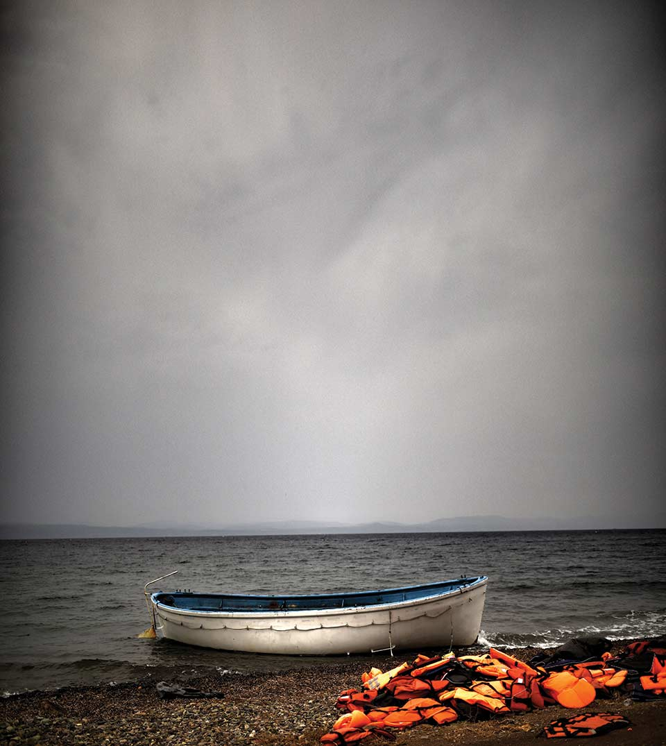 Orange lifejackets piled up on the shore of an island just next to a boat moored nearby. The open ocean and a dark sky looms in the background.