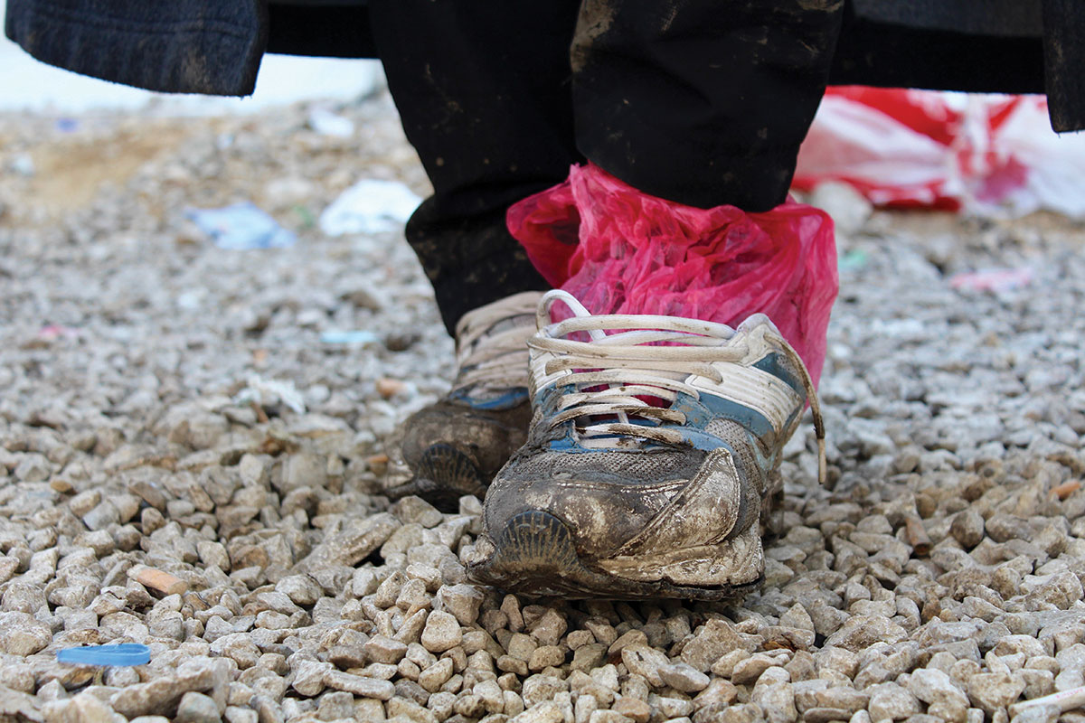 A refugee's shoes are worn, wet, and muddy after a long journey. These shoes are owned by Ali, a Yazidi refugee who traveled from Iraq to Preševo, Serbia, to avoid persecution.  Photo: Meabh Smith / Trócaire