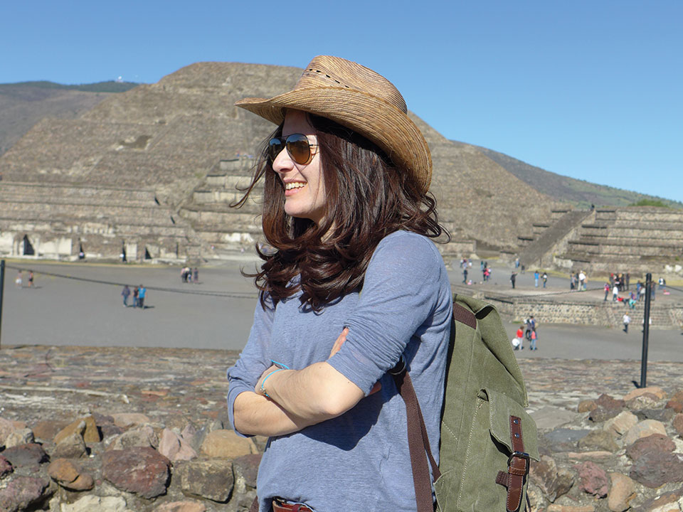 Eleni Kefala stands, arms crossed and smiling, in profile, wearing a straw hat