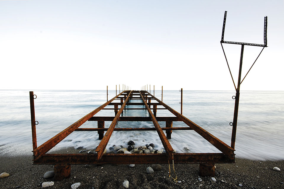 The steel frame of a dock, not covered and thus exposing the sea below, extends out from a rocky beach.