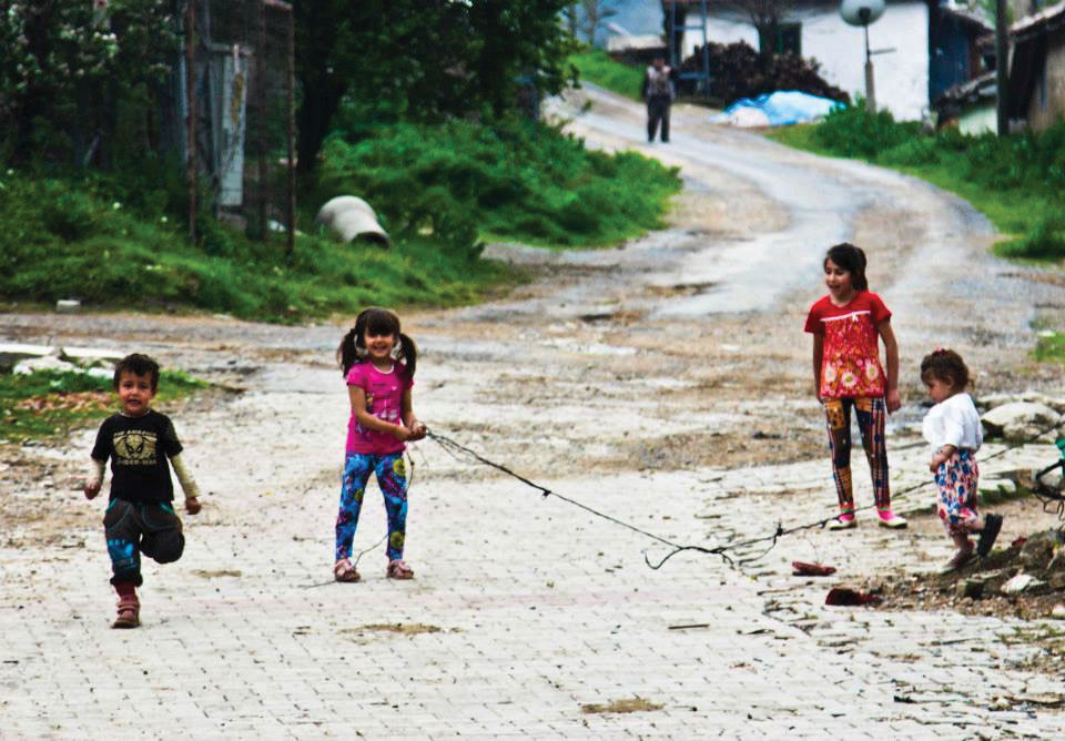 Children idly play tug of war with a discarded piece of chain