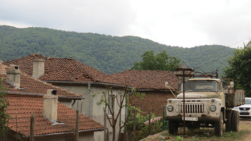 A large truck sits on the road just above a village with forested mountains in the background