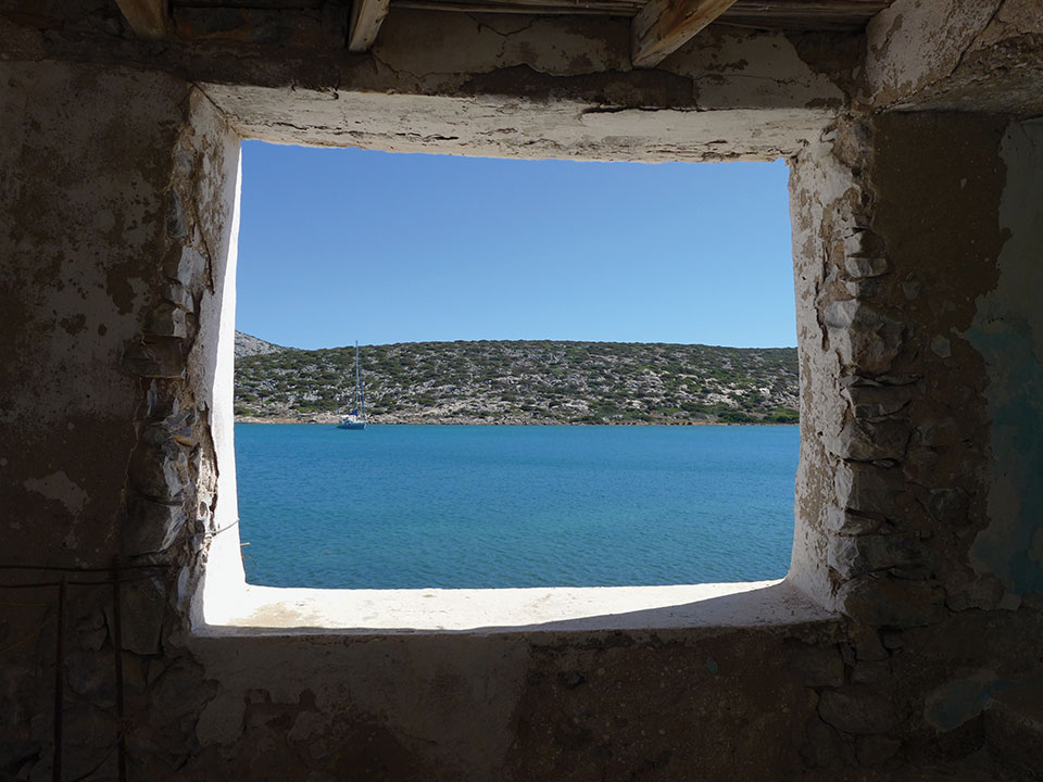 The sea and opposing shoreline as seen through a rugged window