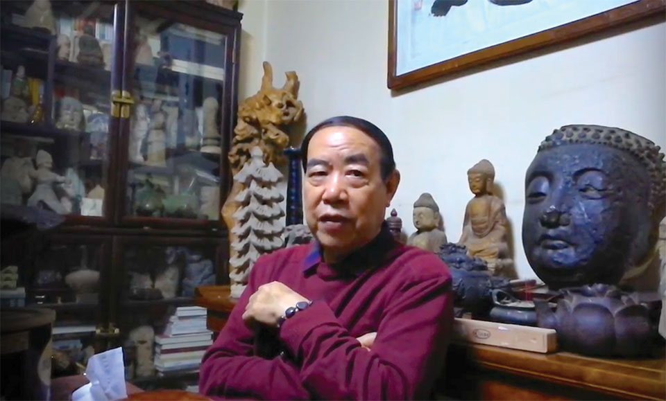 Author Jing Pingwa sits, arms crossed casually, in front of a number of religious icons