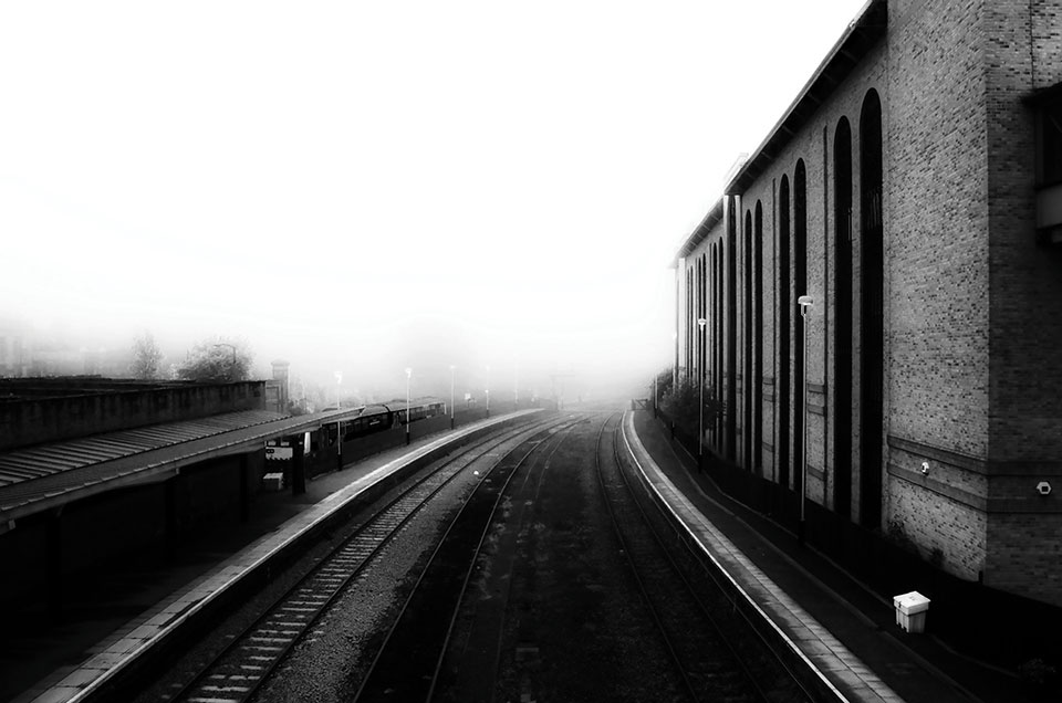 A black and white photo of train tracks stretching into a high-contrast distance