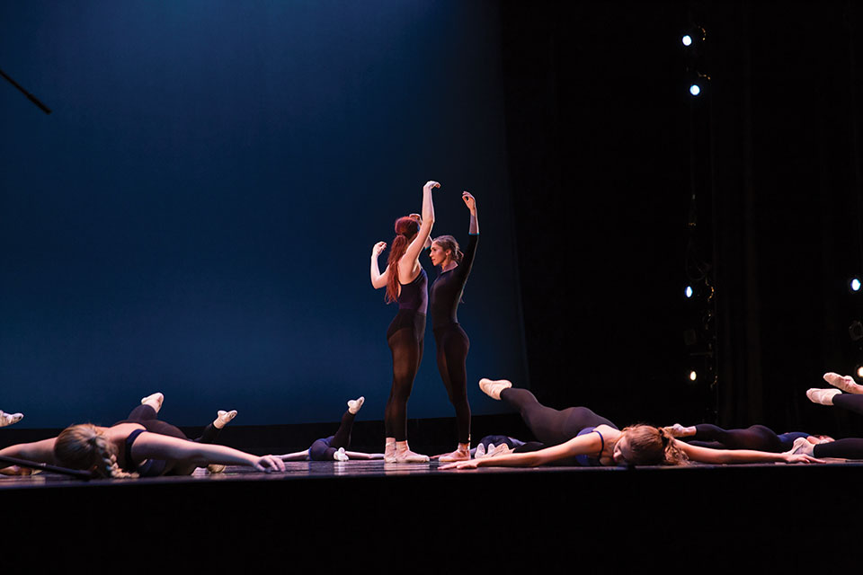 Two dancers stand face to face standing amidst other dancers lying motionless on the stage