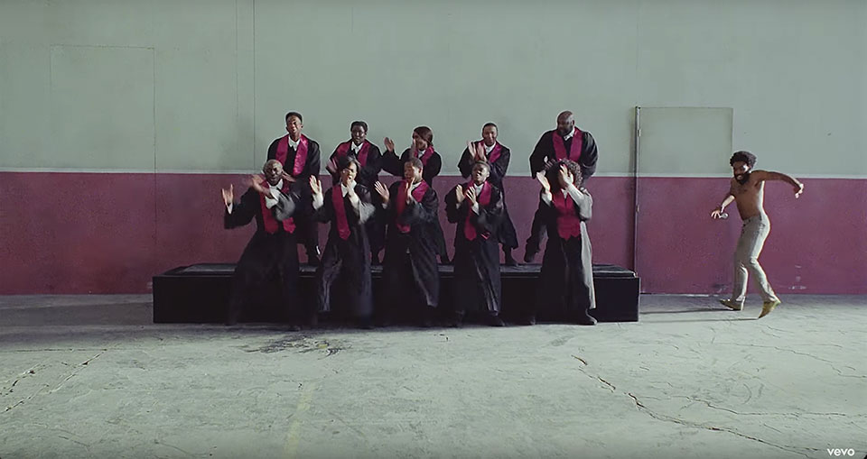 "A still image from the video to Childish Gambino's ""This is America,"" featuring a choir of African-Americans singing on riser as Gambino emerges into the frame from the right"