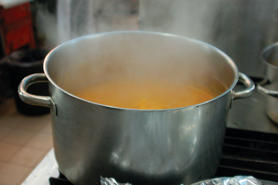 A photograph of a pot of broth steaming on a white stove