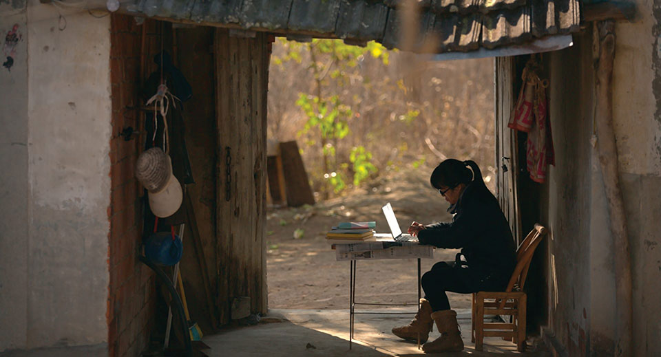 A photograph of Yu Xiuhua writing on a laptop