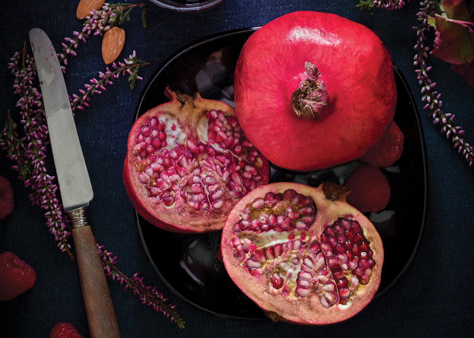 Looking down on a table that has two pomegranates on it, one cut, one uncut, with the knife that opened the one up laying beside it.
