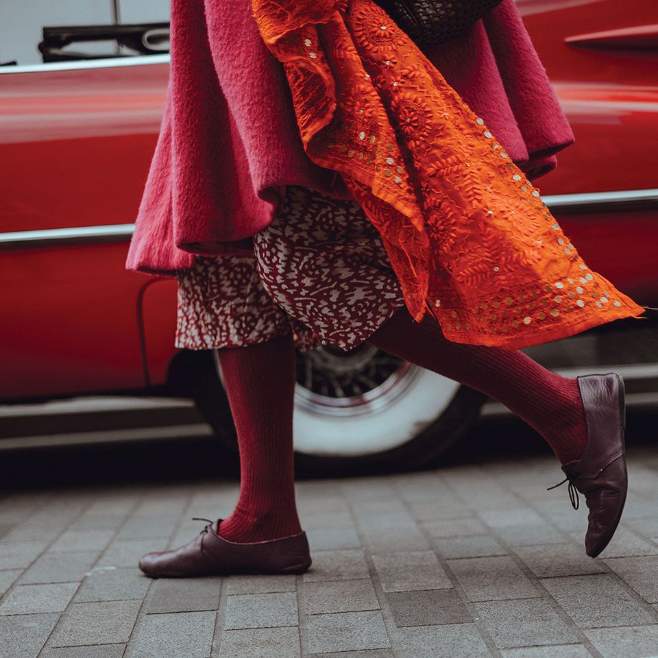 The lower half of a women, dressed mostly in reds and oranges, walking along a busy city street