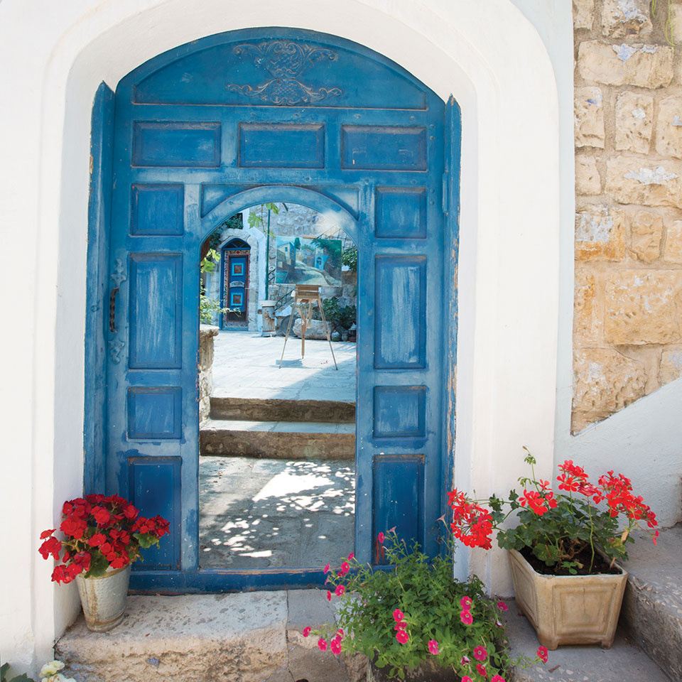 A blue door open before the viewer, revealing a courtyard within, in the city of Safed, Israel