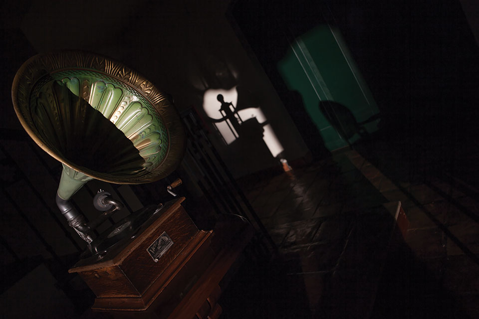 A Victrola, partially draped in shadow, in the foreground as fading light is swallowed up by a room tilted askew in the background