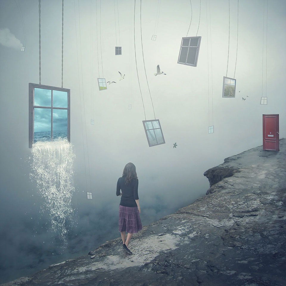 A digitally manipulated photo. A female walks away from the viewer along a cliff's edge towards a red door. Windows hang in the sky nearby, the largest of which is gushing water,.
