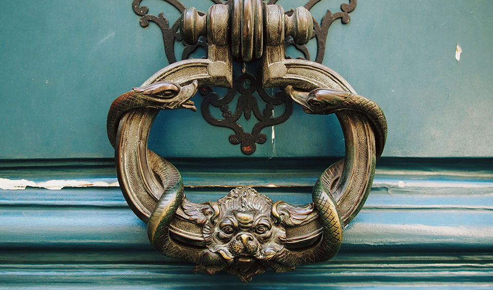 An ornate brass door knocker rests on a dark turquoise door