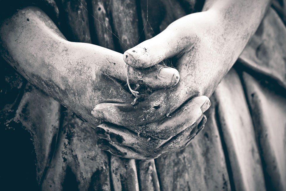 A close-up of the weather worn hands of a angel statue