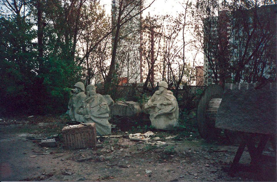 A collection of statues of resting soldiers, tucked into a small grove of trees with trash and industrial detritus strewn about