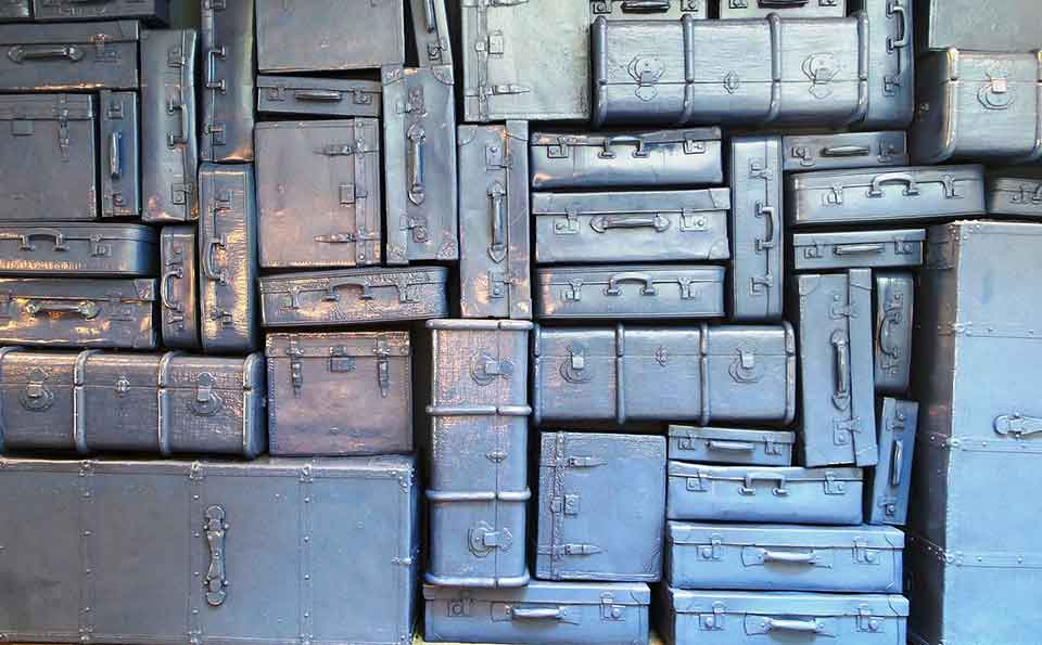 Many pieces of luggage, all spray painted uniformly with a metallic sheen, stacked into a wall