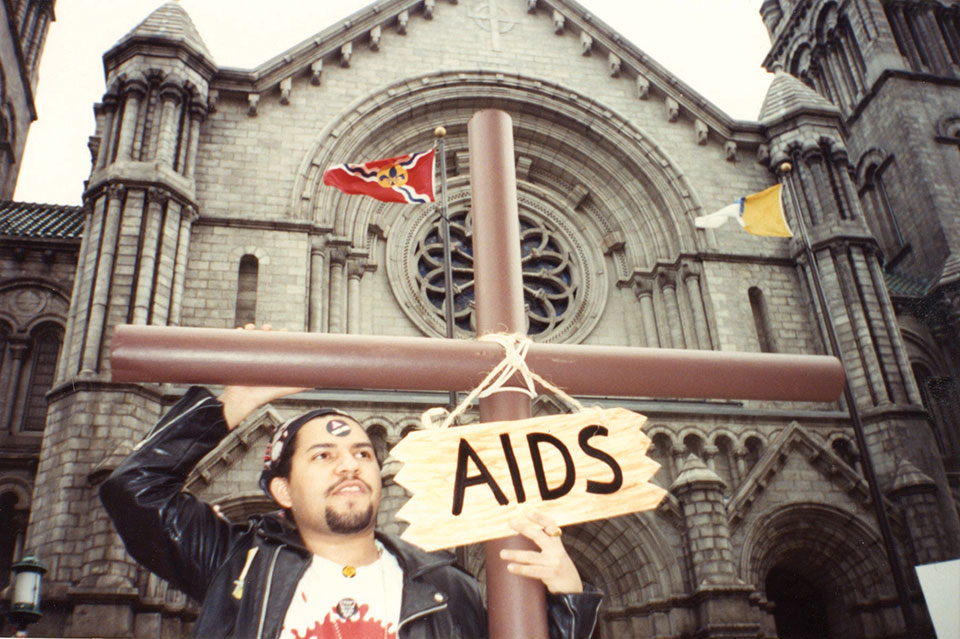 """A man in a leather jacket carries a cross with a sign hanging around it that reads, """"AIDS,"""" while standing in front of a church"""