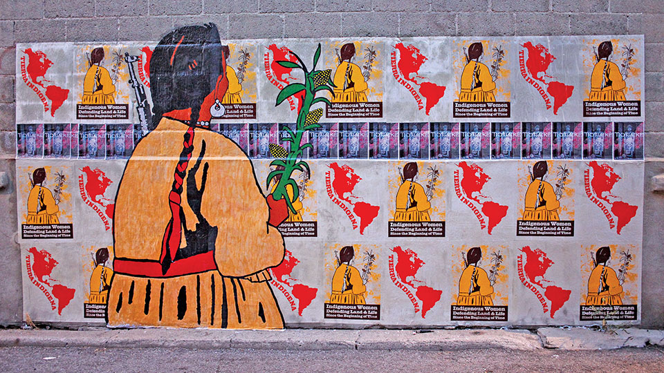 A wall covered in an image dominated by a large human figure that appears to be looking at a recurring pattern of that same figure looking at an outline image of North and South America