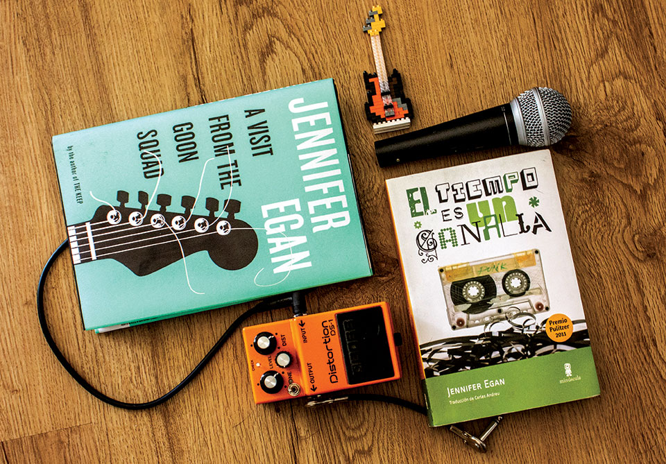 Copies of Jennifer Egan's A Visit from the Good Squad & (in translation) El tiempo es un canalla with a microphone, guitar pedal, and small guitar keychain