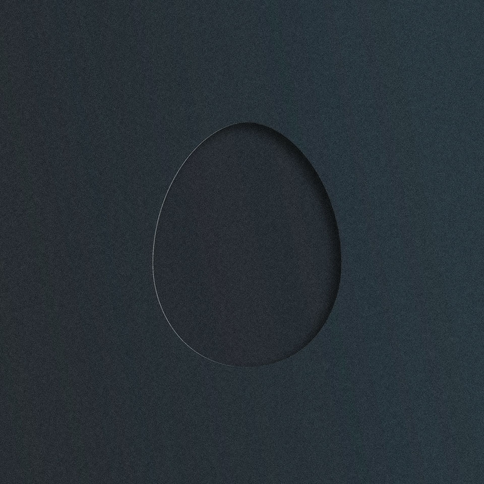 A hole cut out of a piece of black matte card stock, revealing black matte card stock beneath
