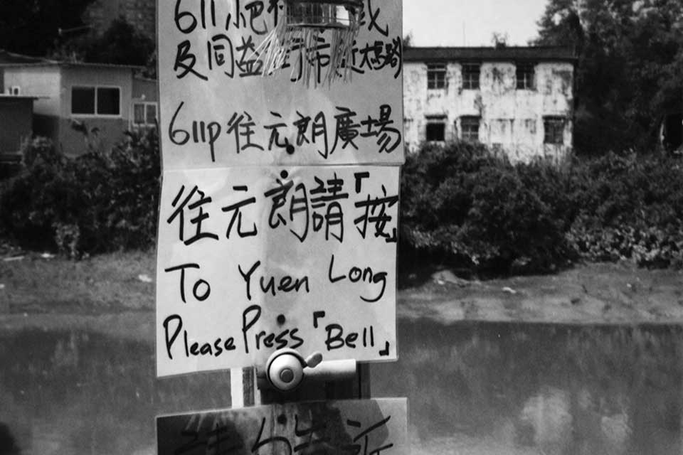 "A hand-lettered sign in Chinese with English words that read ""To Yuen Long / Please Ring Bell"""