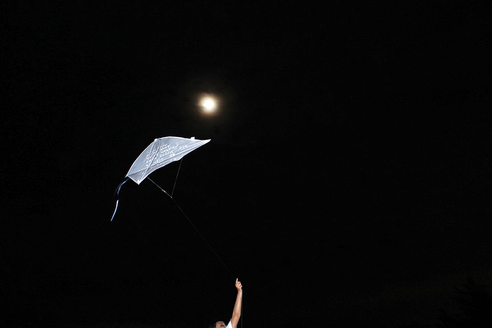 A photograph of a white kite held by an arm that stretches into the bottom of the frame with the moon hovering just above the kite