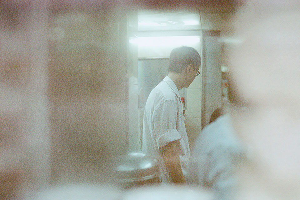 A gauzy photo of a waiter in Hong Kong working in a kitchen