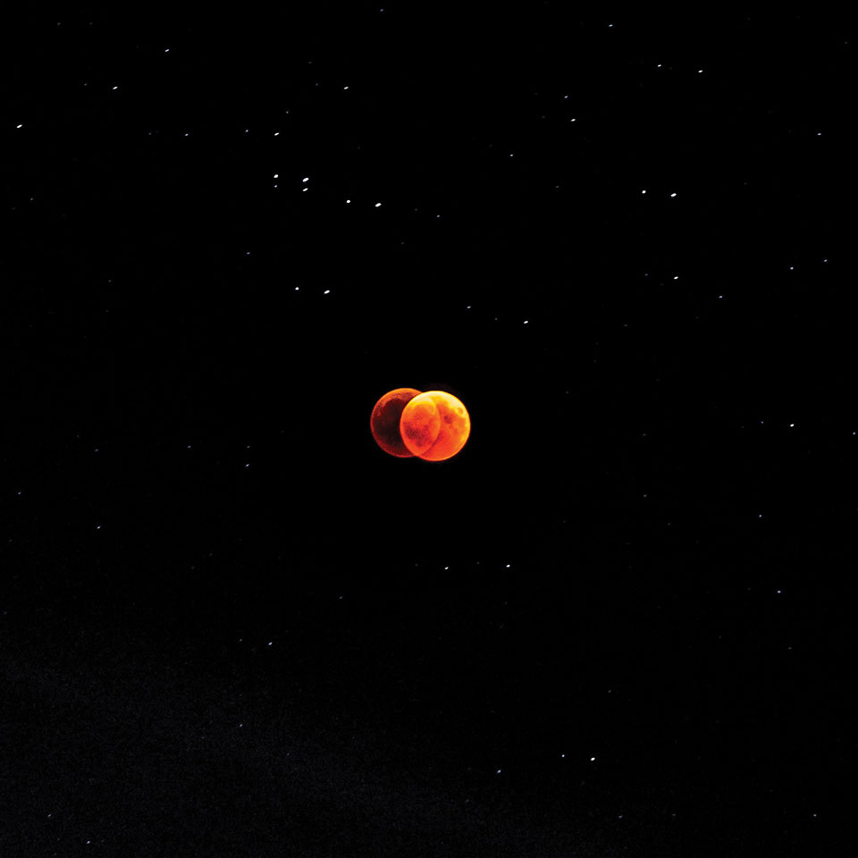 A double-exposed image of the moon, tinged red