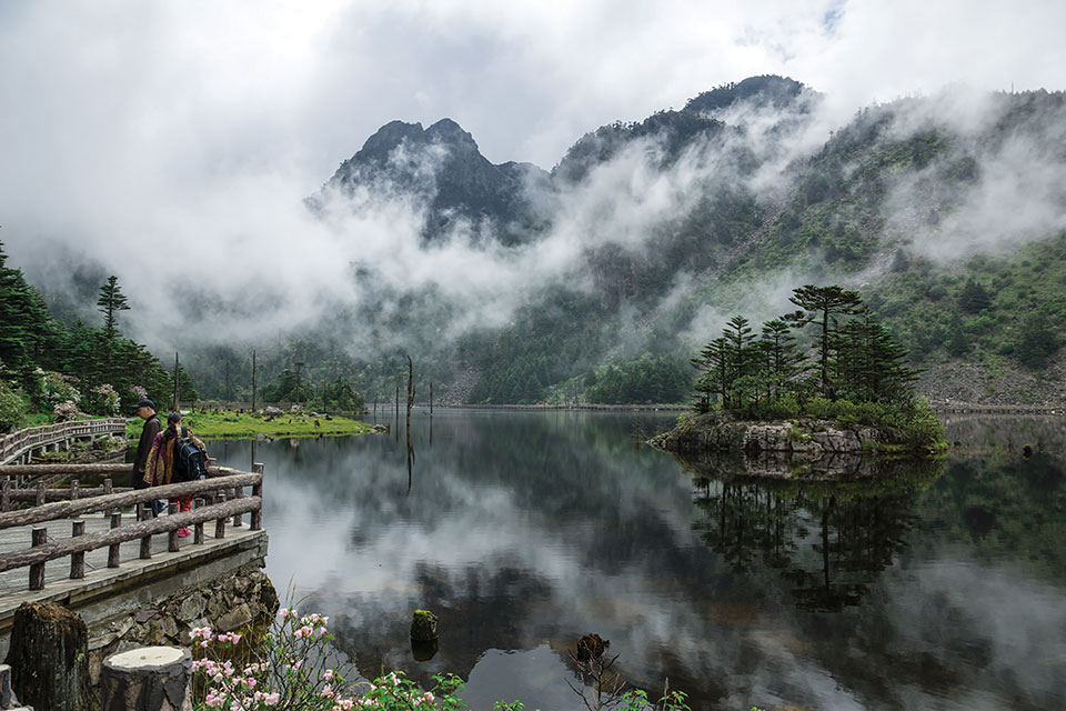 Spectators stand on a stone overlook that juts on to a wooded lake that sits at the foot of foggy mountains