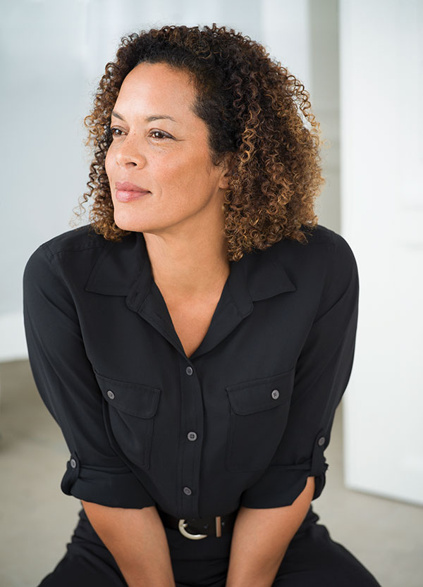 Aminatta Forna sits looking off panel, clad in black