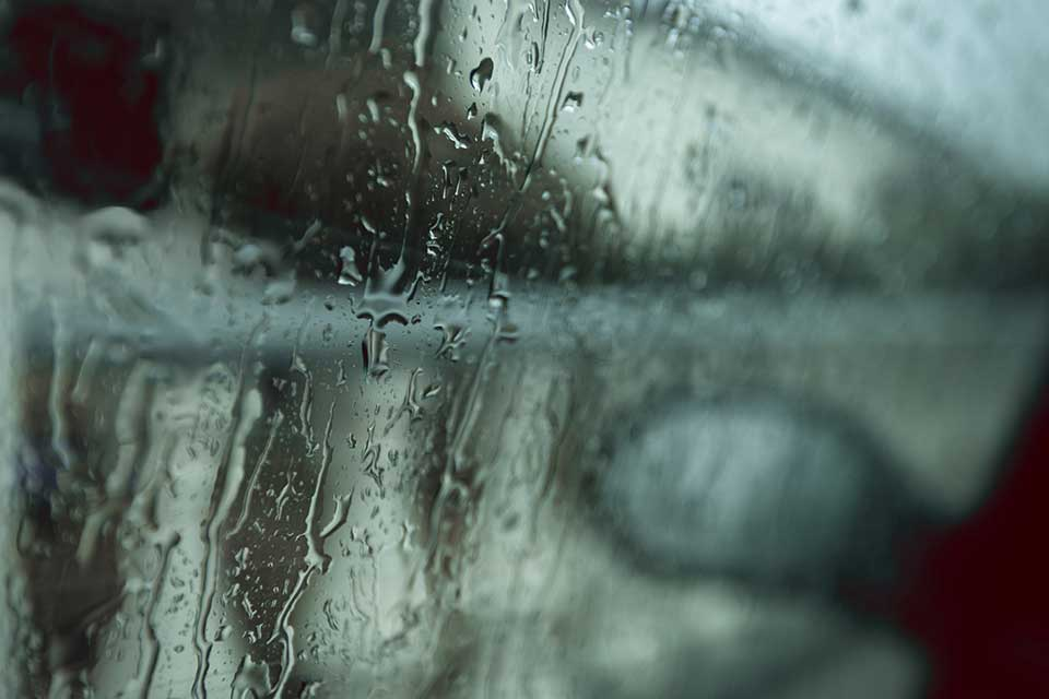 A photograph of a rain-streaked window