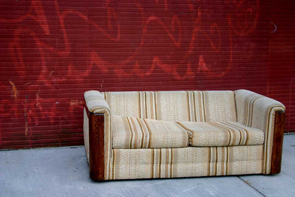 A photograph of a sofa sitting in front of a wall, painted red with faded graffiti still visible