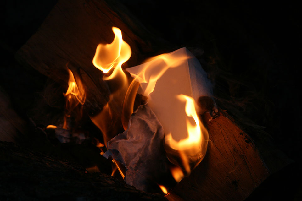 A photograph of paper burning up in a fire at night