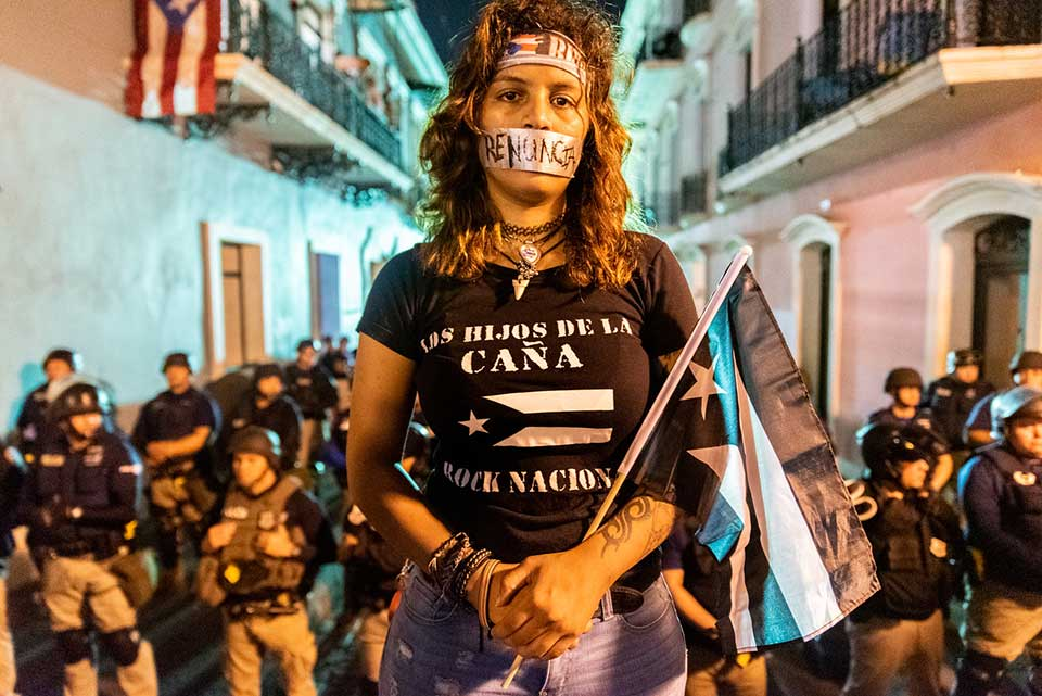 A photograph of a group of protestors staring at the camera