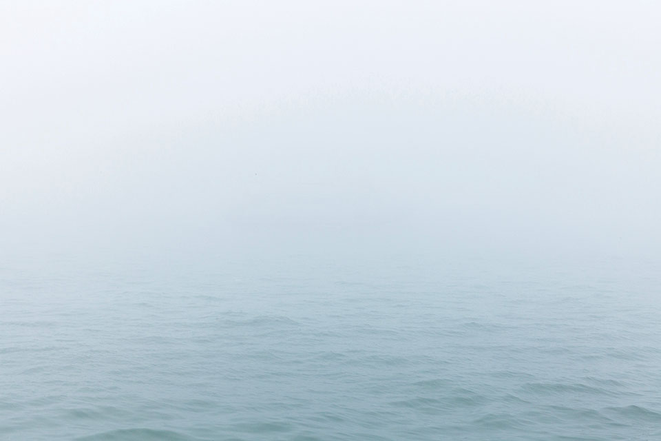 A grey sea shrouded in clouds