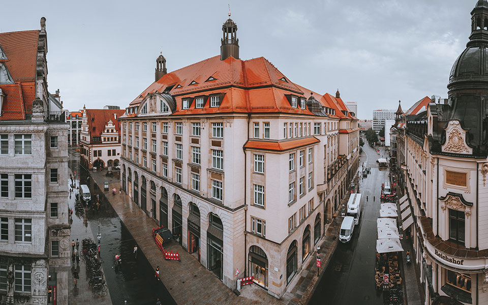 A panaroma shot of Leipzig with a large building protruding in the foreground