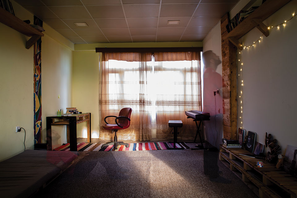 A photograph from inside a room. Curtains block much of the sunlight from the window but a narrow band paints the floor with light. A ghostly half-image of a person looking at the wall can be seen mid-ground