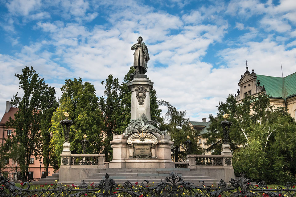 A monument to poet Adam Mickiewicz, surrounded by trees under a blue sky dotted with clouds