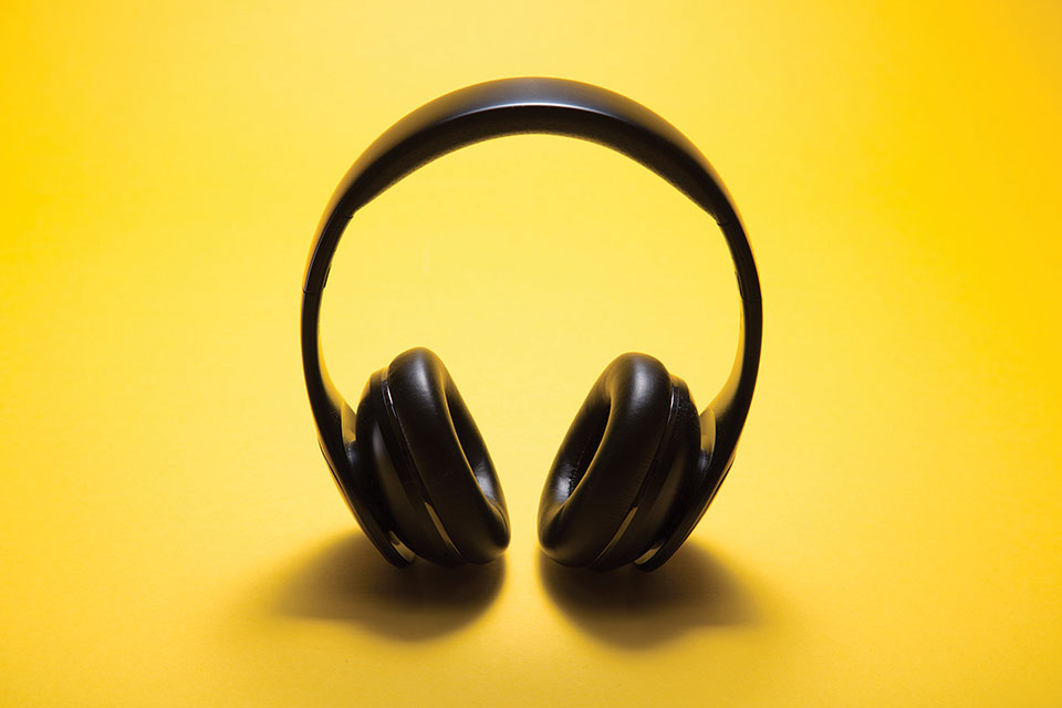 A pair of headphone photographed against a yellow background