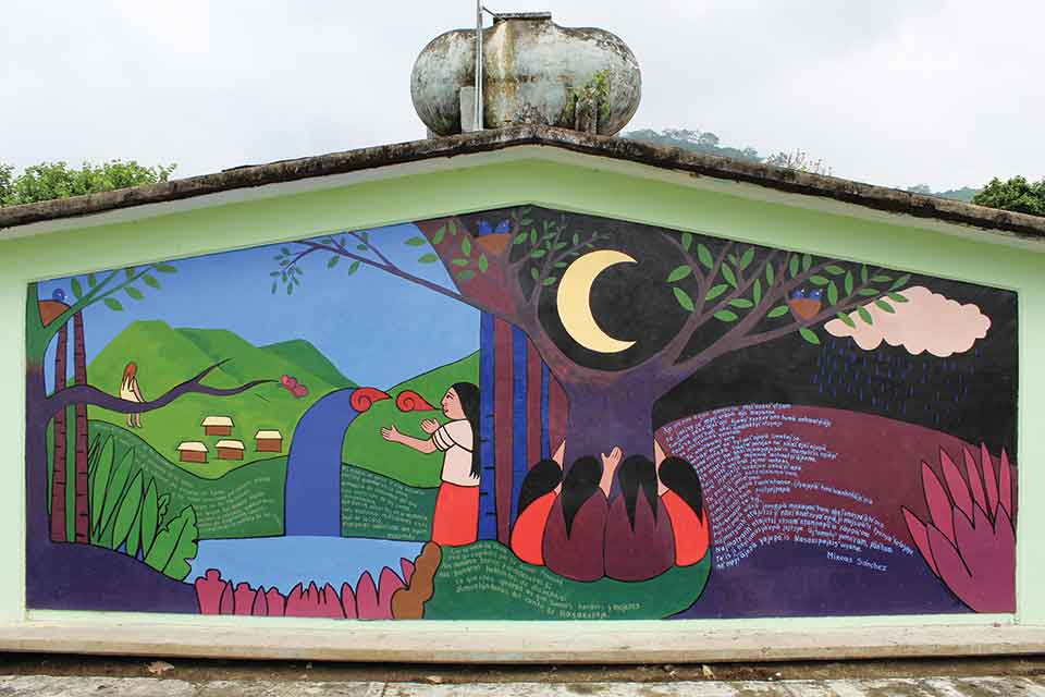A photograph of a mural, containing several human figures, on the side of a building
