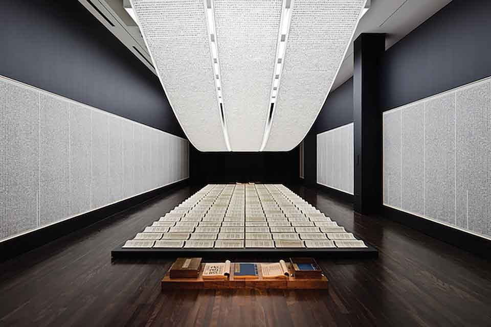A photograph of an art installation. A long table sits beneath a long, curved light. The table is covered with carefully arranged parchment with writing on them.